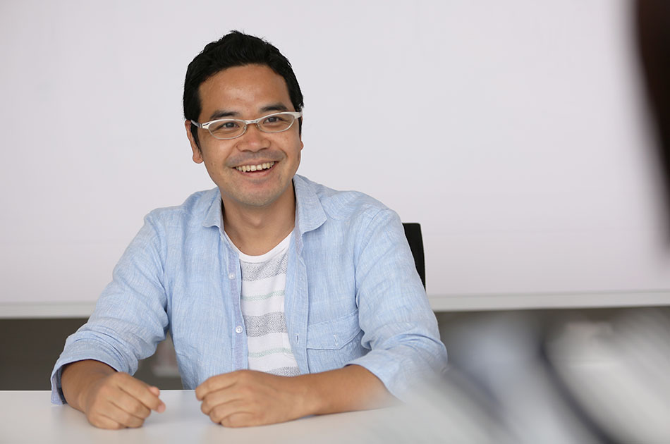 """写真:インタビュアーに笑顔でこたえるサービスマネージャーの田中"""""""