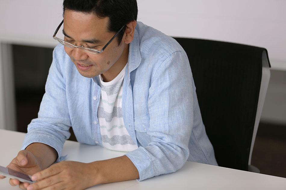 """写真:スマホを片手に説明しているサービスマネージャーの田中"""""""