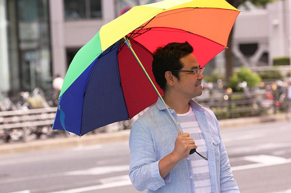 """写真:カラフルな傘をさしているサービスマネージャーの田中"""""""