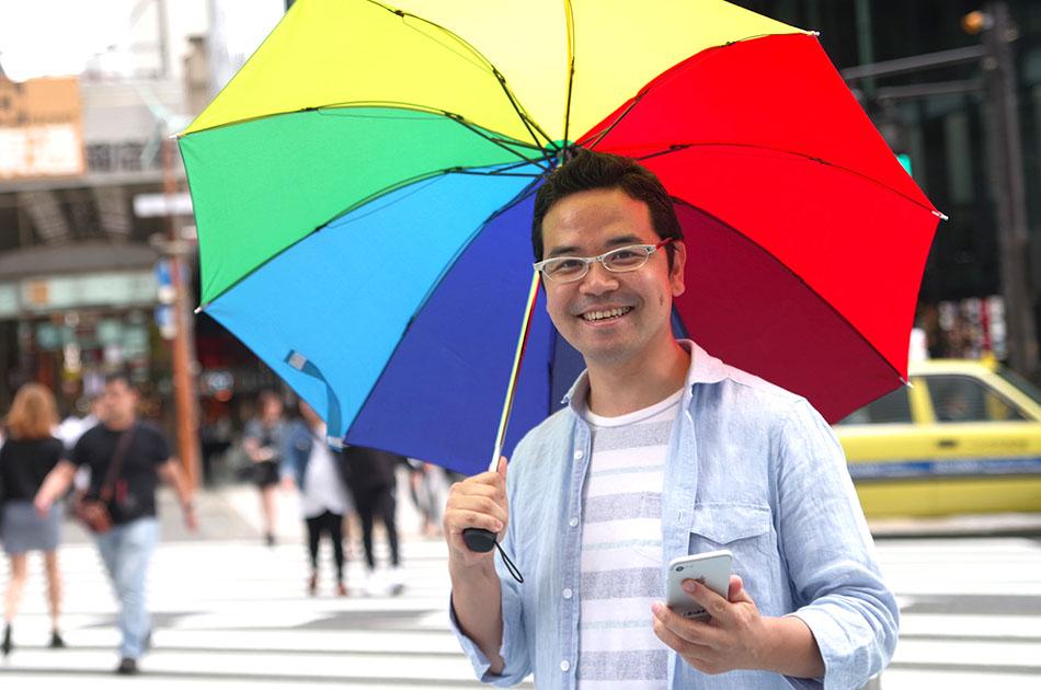 写真:スマホを片手に、カラフルな傘をさしているサービスマネージャーの田中