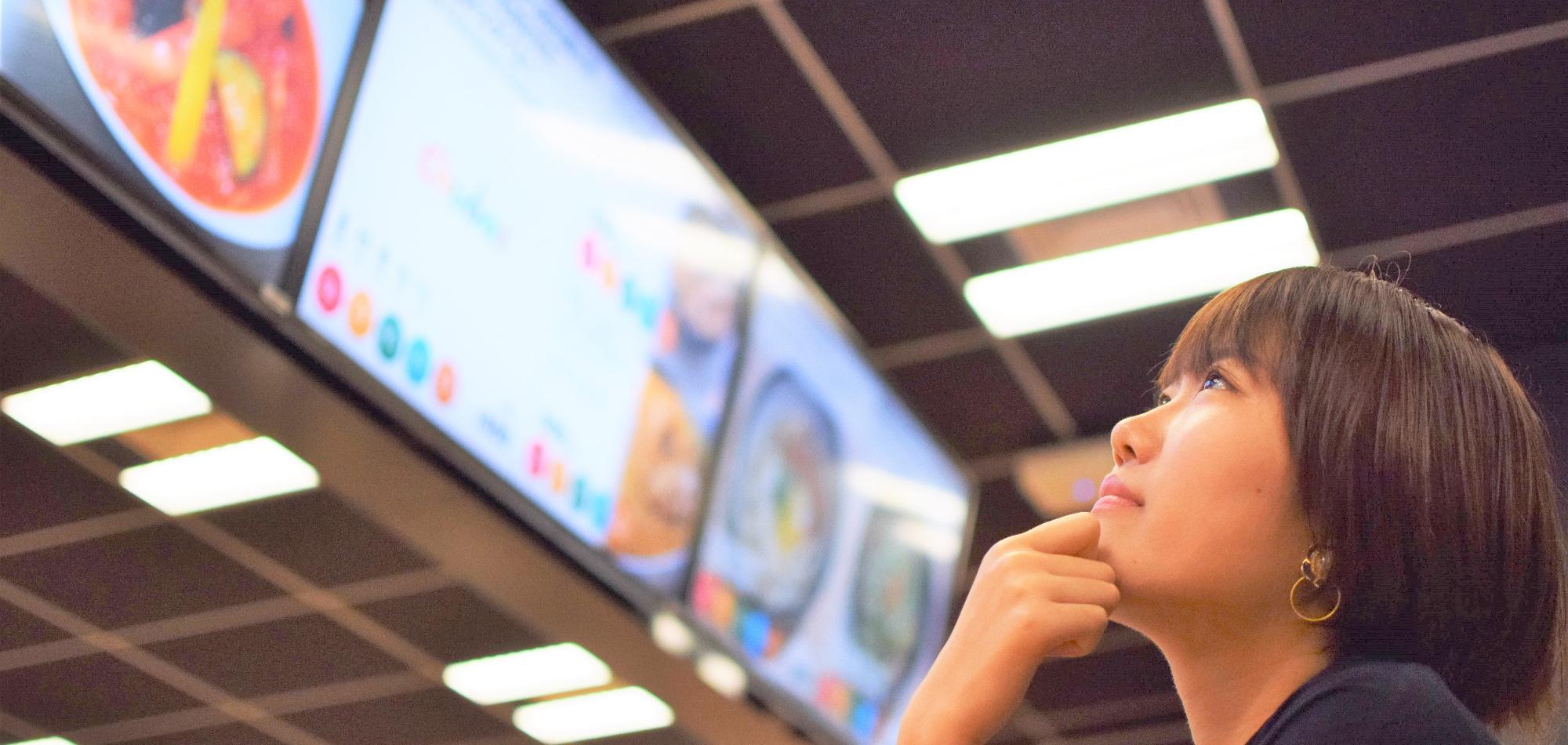2019年新卒入社のいっしきさえが社食でメニューを見ている画像