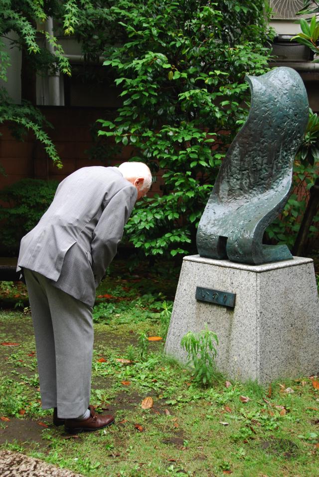 早稲田中学校・高等学校にある慰霊碑に向けて頭を下げる堀内さん=2016年6月