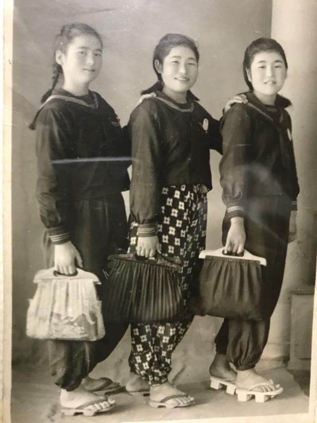 終戦直後、女学校の友だちらと。手作りの布製のカバンを持って写真館で撮影してもらった。左が日高さん。=日高美奈子さん提供