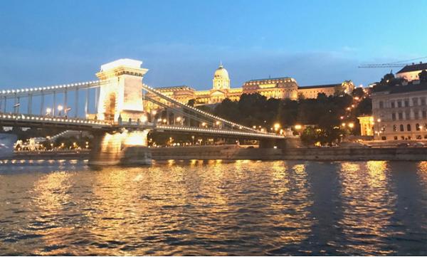 2017年の総会が開かれた、ハンガリーの首都ブダペストの夕暮れ時の写真。町の中心にドナウ川が流れ、鎖橋がブダ側とペスト側を結んでいる。奥にはライトアップされた王宮がみえる。