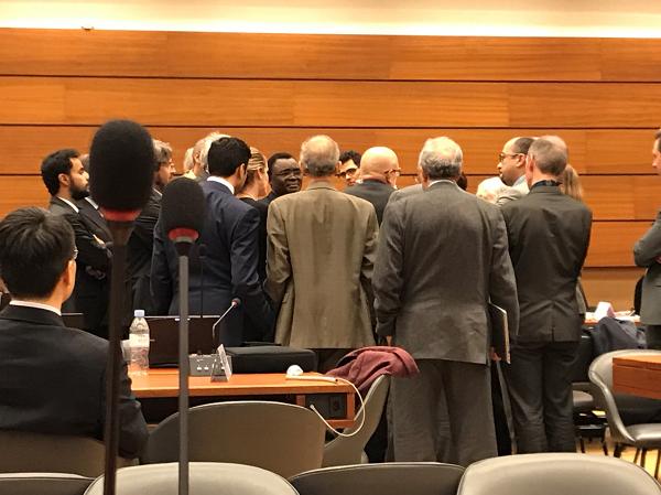 メンバーが一箇所に集まって緊迫した交渉を行っている様子をとらえた写真。
